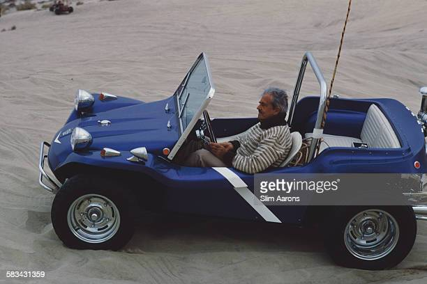 Frenchborn American industrial designer Raymond Loewy driving a dune buggy in the desert near Palm Springs California January 1970