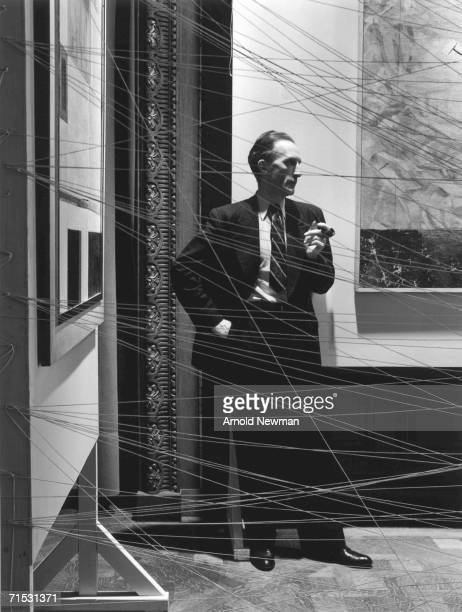 French-born artist Marcel Duchamp holds a pipe as he poses behind his art installation 'Sixteen Miles of String,' New York, New York, 1942.