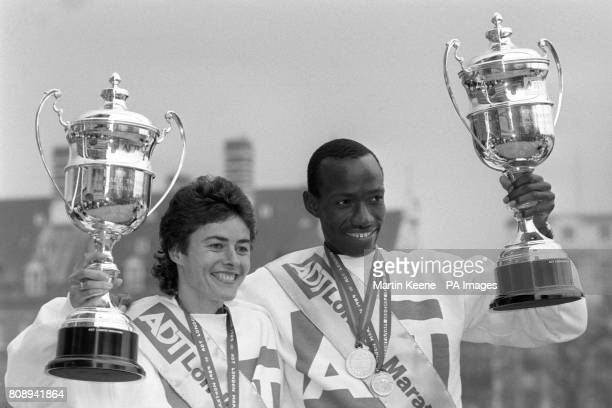 Frenchborn British runner Veronique Marot holds up her trophy for winning the Women's Elite Race with Kenyan Douglas Wakiihuri winner of the Men's...