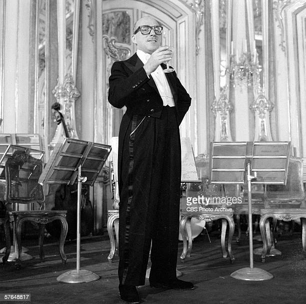Frenchborn composer and conductor Ray Bloch orchestra leader for 'The Ed Sullivan Show' wears a tuxedo and holds a drink as he stands in front of set...