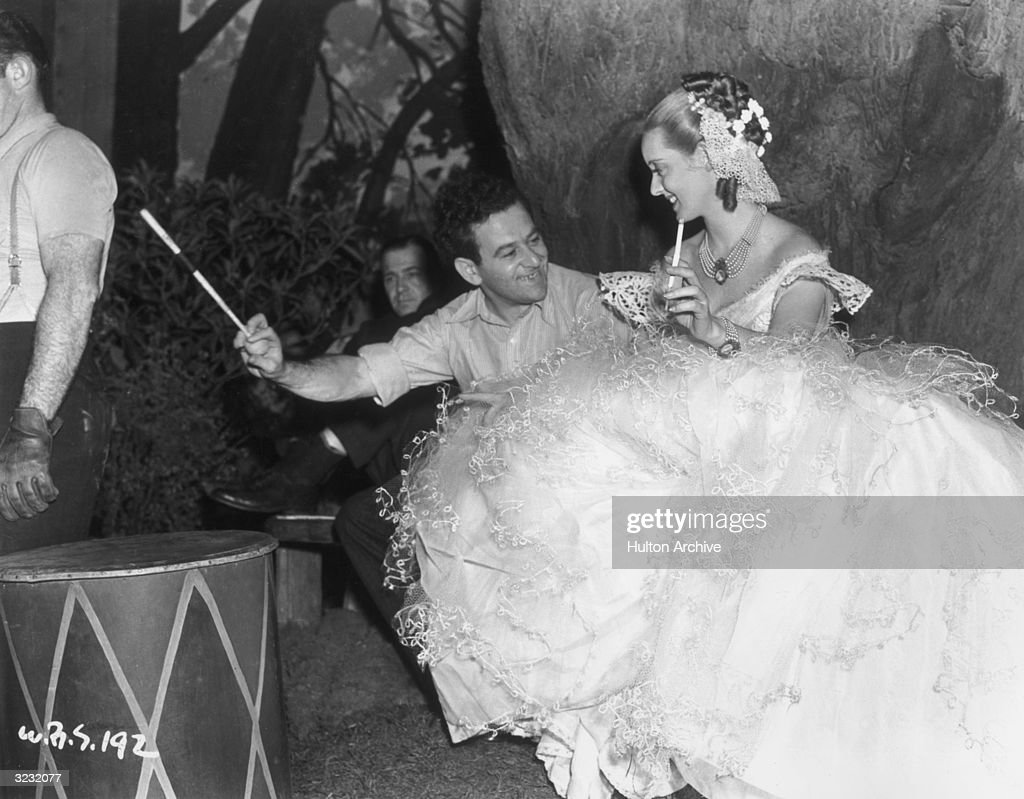 French-born director William Wyler (1902 - 1901) and American actor Bette Davis (1908 - 1989) hold long cigarette filters while laughing on the set of Wyler's film, 'Jezebel,'. Davis is dressed in a white lace gown with a full skirt.