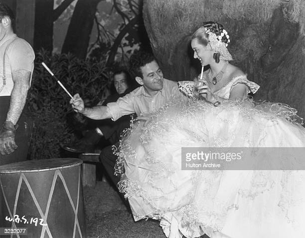 Frenchborn director William Wyler and American actor Bette Davis hold long cigarette filters while laughing on the set of Wyler's film 'Jezebel'...