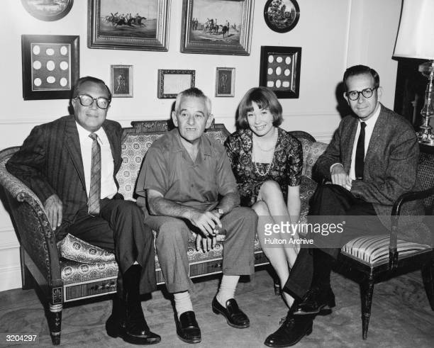 Frenchborn director William Wyler and American actor Shirley MacLaine are flanked by film producer brothers Harold and Walter Mirisch on the set of...