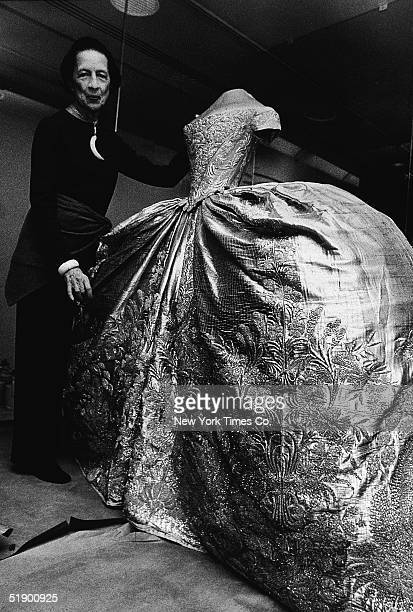 Frenchborn fashion editor Diana Vreeland a special consultant to the Metropolitan Museum of Art displays a silk and silver wedding dress worn by...