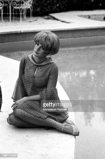 French-born Italian actress Catherine Spaak sitting by the swimming pool. The actress wears a polka dots printed chiffon evening outfit. Rome, 1966.