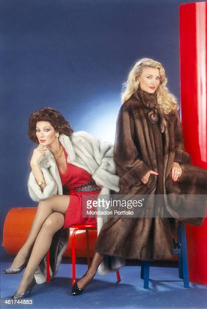 Frenchborn Italian actress Edwige Fenech and Germanborn Italian actress Barbara Bouchet posing wearing a fur coat Italy 1984