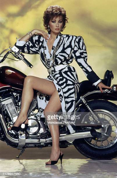 Frenchborn Italian actress Edwige Fenech leaning against a motorcycle 1986