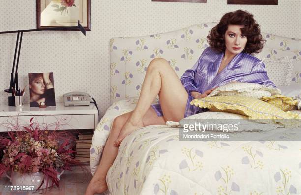 Frenchborn Italian actress Edwige Fenech sitting on a bed 1990