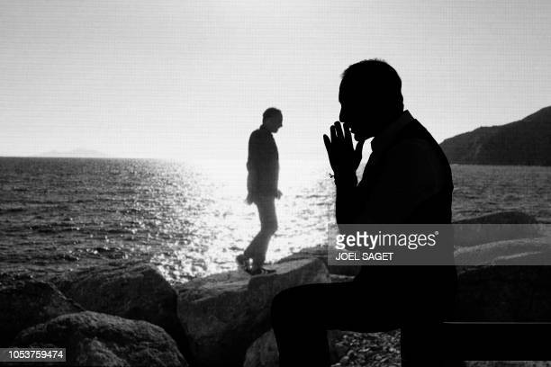 FrenchGreek photographer journalist TV and radio host Nikos Aliagas poses past his photographs during a photo session at his exhibition in Paris on...