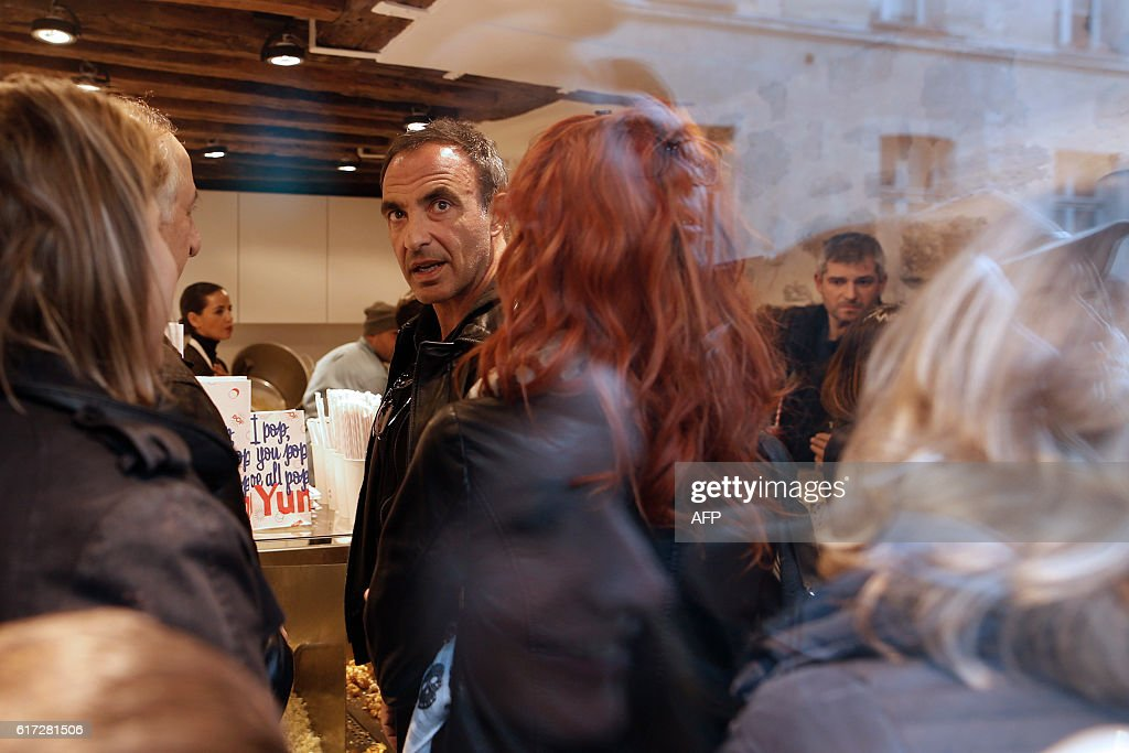 French-Greek TV presenter Nikos Aliagas attends the opening of the Yummy Pop gourmet popcorn shop in the Marais district of Paris on October 22, 2016. The concept is a labour of love between US actress Scarlett Johansson and her French husband, advertising executive Romain Dauriac. And the couple hope that if their 'Real Vermont Cheddar' and other savoury and sweet recipes are a hit, they will open other shops elsewhere. / AFP / Benjamin CREMEL