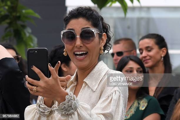 FrenchIranian actress Golshifteh Farahani takes photos on May 13 2018 during a photocall for the film Girls of The Sun at the 71st edition of the...