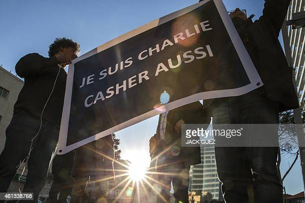 FrenchIsraeli dual nationals hold a sign reading in French 'I am Charlie' during a remembrance ceremony in Tel Aviv on January 11 to protest against...