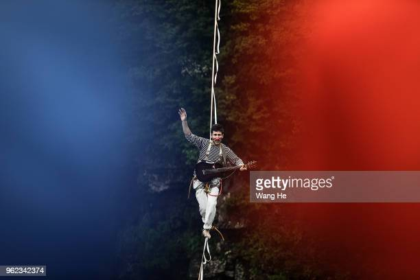 Frenchman Bastien Romero of the band HouleDouse perform on slacklines across the 1400meterhigh cliffs of Tianmen Mountain on May 252018 in...
