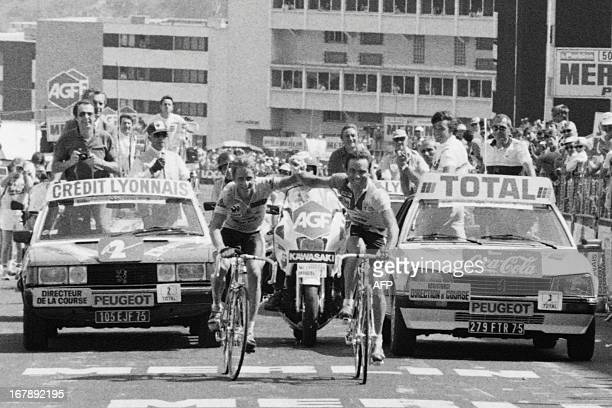 Frenchman Bernard Hinault and his teammate US Greg Lemond smile as they cross the finish line together at the end of the 18th stage of the Tour de...
