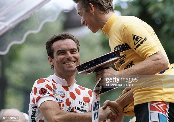 Frenchman Bernard Hinault wearing the red and white Polka Dot Jersey of the best climber second placed in the overall ranking congratulates 27 July...