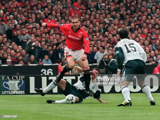 Frenchman Eric Cantona of Manchester United leaps over Robbie Fowler of Liverpool for the ball during the first half of the FA Cup final 11 May 1996...