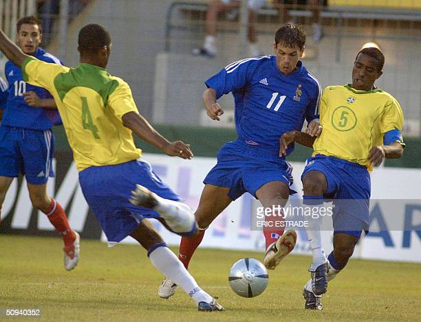 Frenchman Jeremie Aliadiere vies with Brazilians Renato and Carlos Alberto , 08 June 2004, in Toulon, during the semi-final of the International...