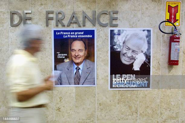 A Frenchman passes in front of photos of French presidential candidates Jacques Chirac and JeanMarie Le Pen pasted to the wall of the French Consul...
