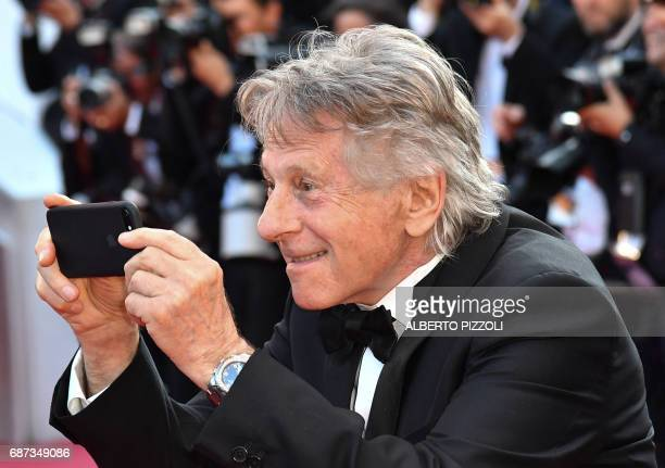 TOPSHOT FrenchPolish director Roman Polanski takes photos as he arrives on May 23 2017 for the '70th Anniversary' ceremony of the Cannes Film...