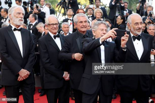 FrenchPolish director Roman Polanski takes photos as he arrives on May 23 2017 with Austrian director Michael Haneke British director Ken Loach...