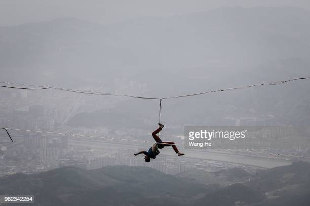 The tourists use selfie sticks to take pictures with their phones as the band HouleDouse perform on slacklines across the 1400meterhigh cliffs of...