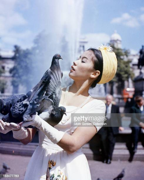 FrenchVietnamese actress France Nuyen feeding pigeons in Trafalgar Square London circa 1962