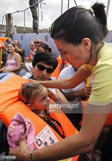 Frenchwoman Ghada Lenoir puts a life jacket on her 20monthold daughter Eliana during their evacuation by the French navy aboard the amphibious war...
