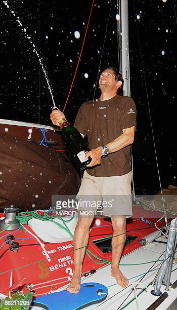 "Frenck Erwan Tabarly, skipper of monohull ""Athema"" sprays champagne on April 25, 2009 upon his arrival at Grand-Bourg harbour on Marie-Galante island..."