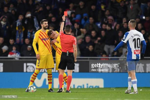 Frenkie de Jong of FC Barcelona is consoled by teammate Gerard Pique as he is shown a red card during the La Liga match between RCD Espanyol and FC...
