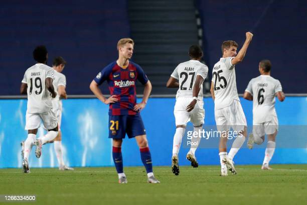 Frenkie de Jong of FC Barcelona looks dejected after Thomas Mueller of FC Bayern Munich celebrates after his team's first goal during the UEFA...