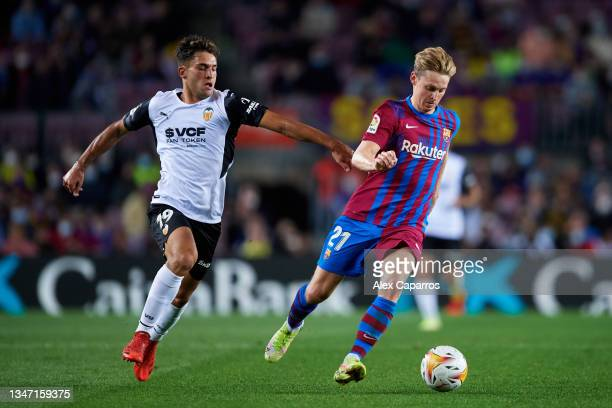 Frenkie De Jong of FC Barcelona runs with the ball under pressure from Hugo Duro of Valencia CF during the LaLiga Santander match between FC...