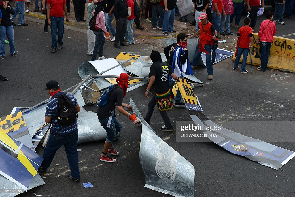 Frente Nacional de Resistencia Popular (FNRP) opposition front activists vandalize billboards during a protest march against violence, in Tegucigalpa, on January 24, 2012. AFP PHOTO / Orlando SIERRA.