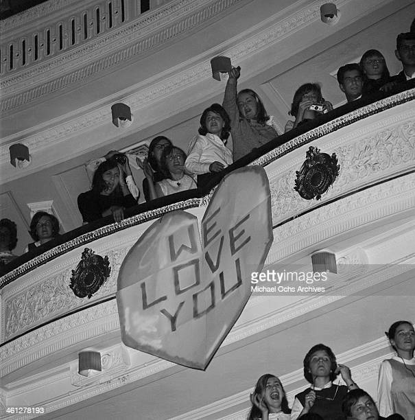 Frenzied fans of the rock and roll band 'The Beatles' cheer and hold signs of encouragement during their concert at Carnegie Hall on February 12 1964...