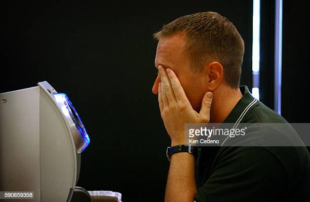 Frequent flyer Lynden Armstrong of Washington DC has his eye scanned in during processing for the Registered Traveler Pilot Program at Ronald Reagan...