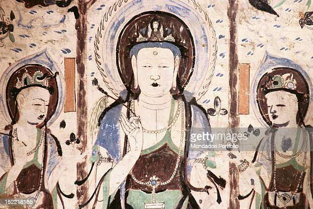 A frescoed wall of one of the hundreds temples dug inside Mogao caves that depicts Buddha meditating surrounded by two Bodhisattvas carrying lotus...