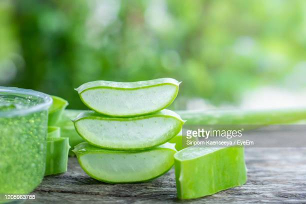 fresh aloe vera leaves slice and aloe vera gel on wooden table - aloe stock pictures, royalty-free photos & images
