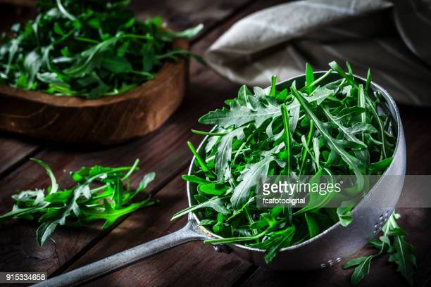 fresh arugula in an old metal colander - rocket stock pictures, royalty-free photos & images