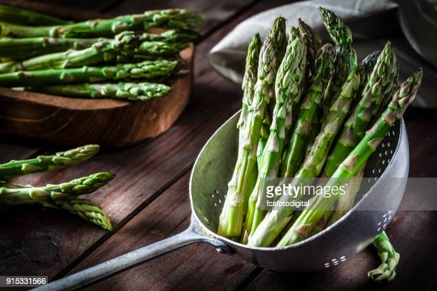 Fresh asparagus in an old metal colander