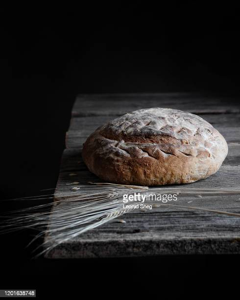 fresh baked homemade bread on wooden table on dark background in minimalism style - pane integrale foto e immagini stock