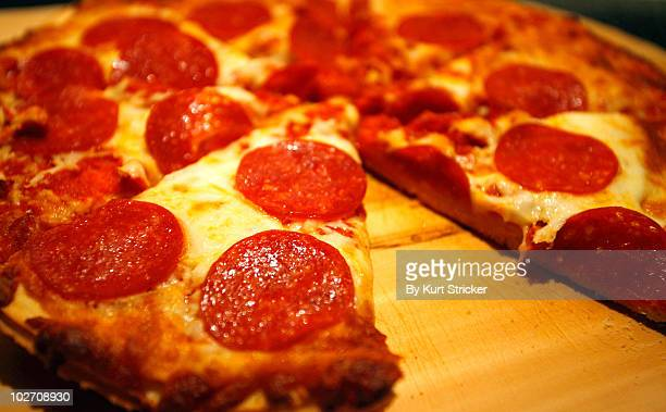 fresh baked pizza on a wooden board - pepperoni pizza stock photos and pictures