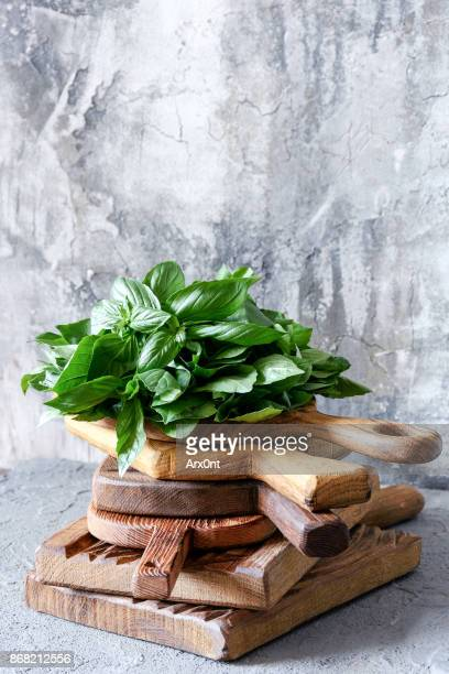 fresh basil on wooden cutting board - mediterrane kultur stock-fotos und bilder