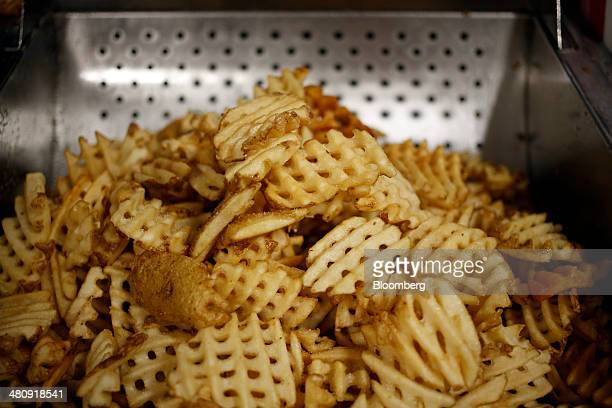 A fresh batch of waffle fries sit before being served at a ChickfilA Inc restaurant in Bowling Green Kentucky US on Tuesday Mar 25 2014 The US...