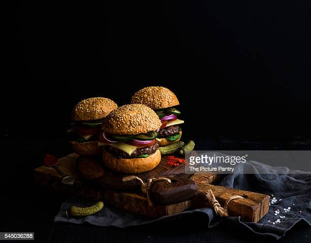 Fresh beef burgers with cheese, vegetables, pickles and spicy tomato sauce on paper on rustic wooden boards, black background