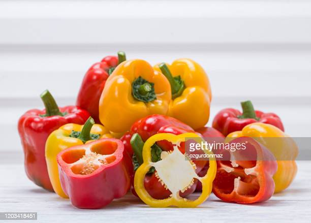 fresh bell peppers on white wood background - yellow bell pepper stock pictures, royalty-free photos & images