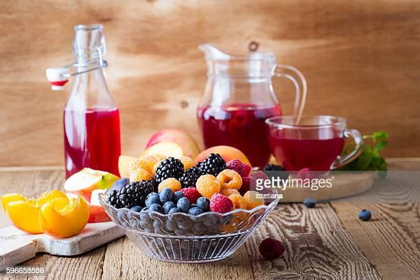 Fresh berries and fruits in  glass bowl, summer fruit tea with raspberries, blackberries and blueberries