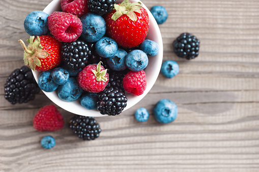 Fresh berries in a basket on rustic wooden background. 521432062