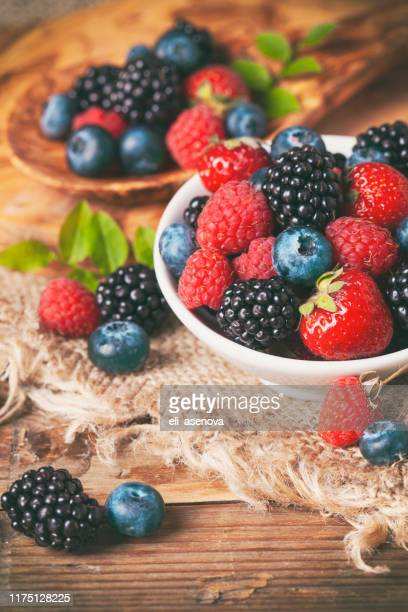 fresh berries in a bowl on rustic wooden background. - blackberry fruit stock pictures, royalty-free photos & images