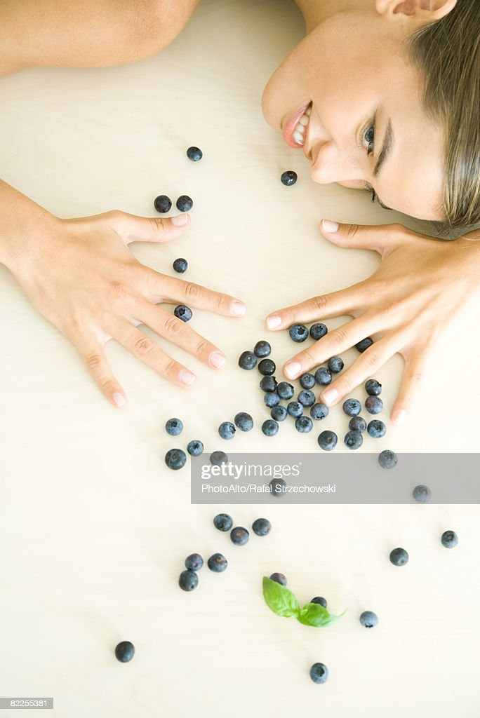 Fresh blueberries scattered across counter, young woman spreading hands over them : Stock Photo