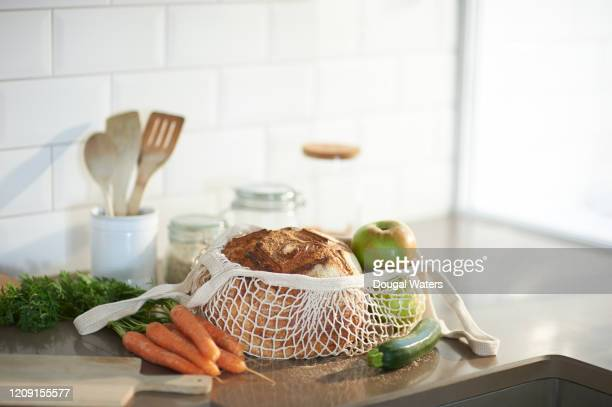fresh bread, organic vegetables and fruit on a plastic free zero waste kitchen worktop. - man made object stock pictures, royalty-free photos & images