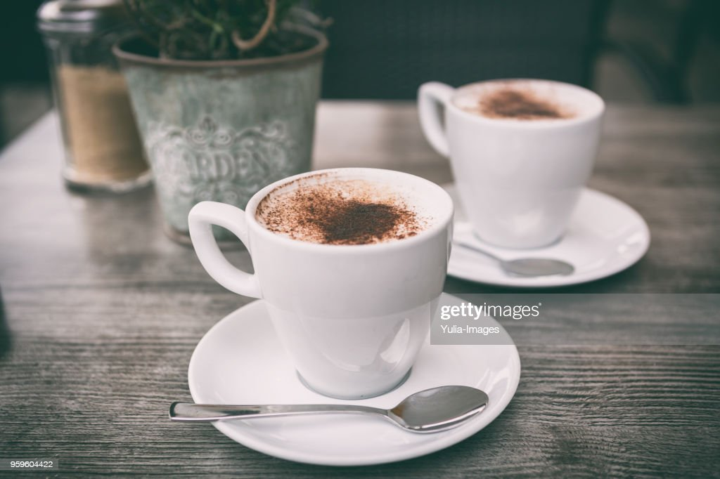 fresh brewed cappuccino coffee with milk in a white cup on table : Stock-Foto